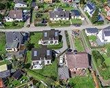 Luftaufnahme eines Grundstückes mit einer 3D-Visualisierung zweier Wohnimmobilien