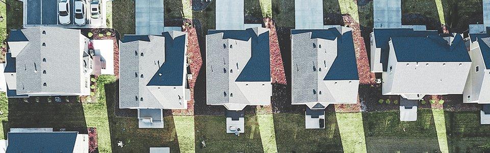 Drohnenaufnahme von weißen Wohnimmobilien mit grauen Dächern