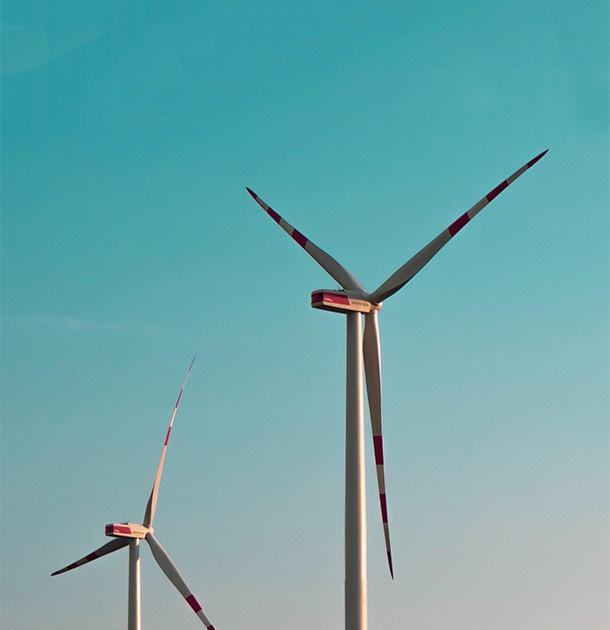 Aufnahme zweier Windräder mit blauem Himmel