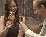 Bild zweier mit Getränken anstoßenden Hotelgäste