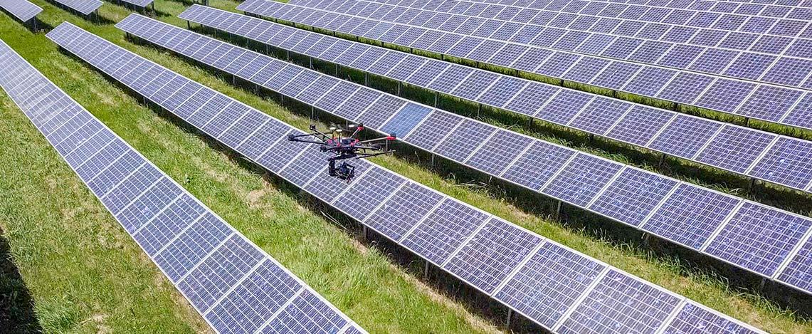 Drohne fliegt über Solarpanel mit Highlight auf Auslesen der Seriennummer.