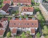 Drohnenaufnahme eines großen Mehrfamilienhauses mit rotem Dach
