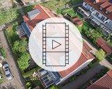 Drohnenvideo mehrerer Wohnimmobilien mit roten Dächern und deren Umgebung