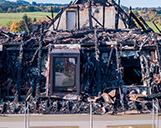 Nahaufnahme aus der Luft von den Fenstern eines abgebrannten Daches