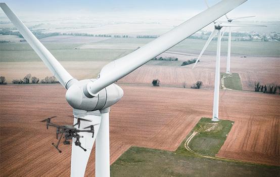 Luftaufnahme einer Drohne mit Windrad mit Feldern und weiteren Windrädern im Hintergrund
