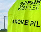 Drohnenpilot mit gelber Warnweste vor einem Windrad