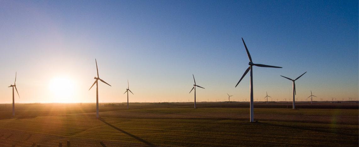 Luftaufnahme von vier Windrädern auf Feld bei blauem Himmel